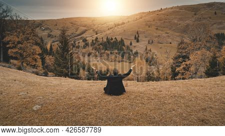 Business man rise-up hands at sun mountain aerial. Rural recreation at pine forest. Countryside nature landscape at autumn day. Businessman mountaineering lifestyle. Carpathian mounts, Ukraine, Europe
