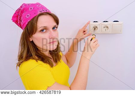 Diy Electrical Outlets Repair. Woman With A Screwdriver Repairs A Broken Outlet