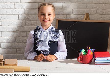 Smiling School Girl Wearing School Uniform In Classroom At School. Portrait Of Lovely School Girl In
