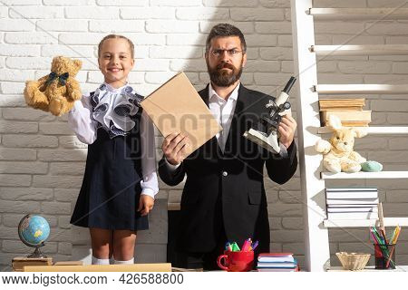 Elementary Pupil With Teacher In Classroom. Teacher With A Young Student Girl At The Elementary Scho