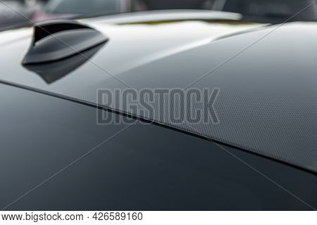 Part Of Carbon Roof Of The Car. Modern Design Sport Car Radio Antenna Also Known As Shark Fin. Close
