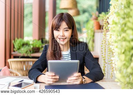 Happy Young Attractive Business Woman In Her Casual Suit Smiling At Camera While Working On Her Comp