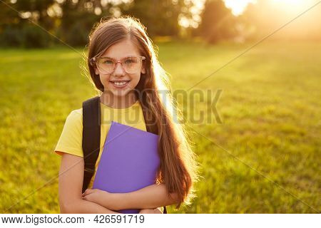 Positive Smart Preteen Schoolgirl In Casual Clothes And Eyeglasses With Backpack And Copybook, Smili