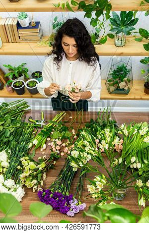 Attractive Young Woman Florist Is Working In A Flower Shop.