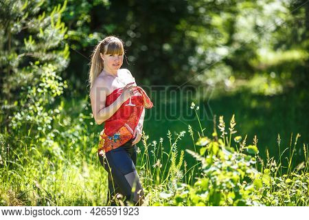 Beautiful Girl With Red Scarf Stands In Thicket Of Forest