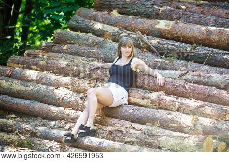 Beautiful Girl Sitting On Cut Logs In The Forest