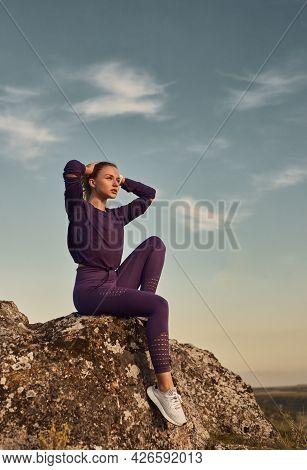 Low Angle Of Young Female In Sportswear Sitting On Rock And Looking Away While Relaxing Alone After
