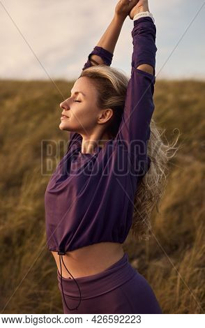 Peaceful Young Fit Female In Sportswear Stretching Arms And Enjoying Freedom And Seclusion While Res