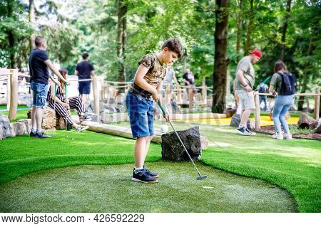 School Kid Boy Playing Mini Golf With Family. Happy Child Having Fun With Outdoor Activity. Summer S