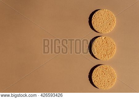 Yellow Facial Cellulose Sponges On Brown Background. Make Up Removal, Spa Procedures At Home.