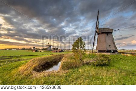 Three Traditional Wooden Windmills In Old Agricultural Landscape Near Schermerhorn, North Holland. N