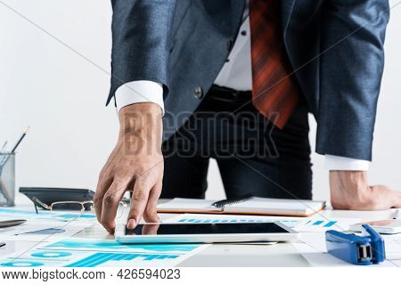Businessman Standing Near Office Desk And Using Tablet Computer. Banking And Financial Management. C