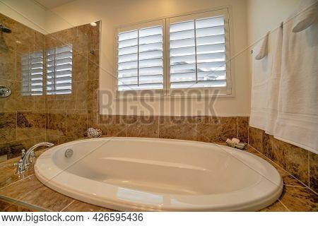 Bathroom With Warm Lightning, Tub, Shower Head And Jalousie Windows