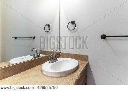 Sink With Granite Countertop And A Mirror Inside The Interior Of A Bathroom