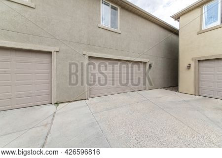 Exterior Of Two Buildings With Concrete Driveway, Garage Doors And Windows