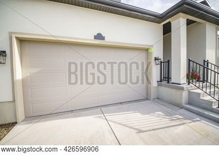 Exterior Of A House With Closed Garage Door And Part Of A Porch Entry With Stairs
