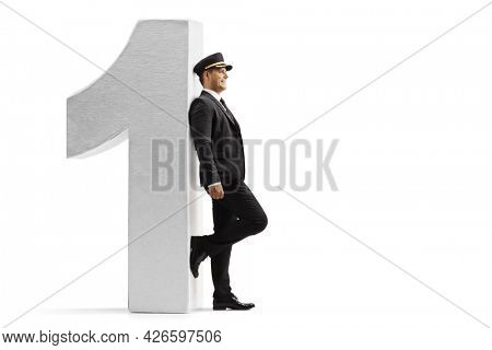 Full length profile shot of a chauffeur leaning on a wall and waiting isolated on white background