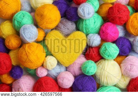Colorful Background Of Multi-colored Yarn For Knitting, Crocheting,in The Middle Of A Yellow Woolen