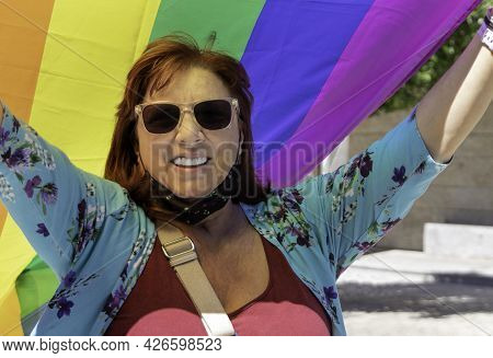 Happy Mature Woman, Smiling And Holding A Rainbow Gay Pride Flag - Gay Pride Concept And Old Age