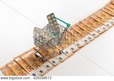 Shopping Cart Full Of Tablets On The Road From Fifty-euro Banknotes, Isolated On White, Copy Space