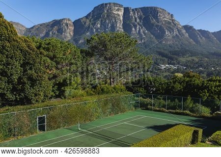 General view of tennis court in stunning countryside on sunny day. retreat, leisure time facilities and active lifestyle concept.