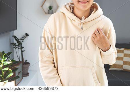 Woman Wearing Beige Sweatshirt Hoodie Mock Up. Mothers Day Mockup In Light Home Interior