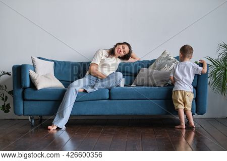 Tired Young Mother Or Nanny Sits On The Couch With Her Eyes Closed Trying To Rest While Her Son Play