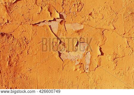 Old Shabby Brown Uneven Plaster. Bright Orange Background Of Street Facades
