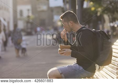 Man With Backpack Eating Street Food In Historical City. Tourist In Old Town Of San Cristobal De La