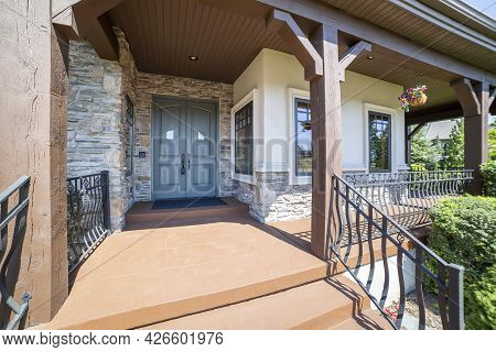 Porch With Gray Double Entry Doors Beside The Windows And Stone Walls