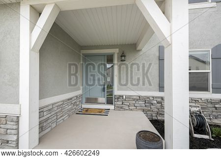 Front Porch With Light Gray Door With Side Window Glass Panel, Doormat And Stone Bricks Wall