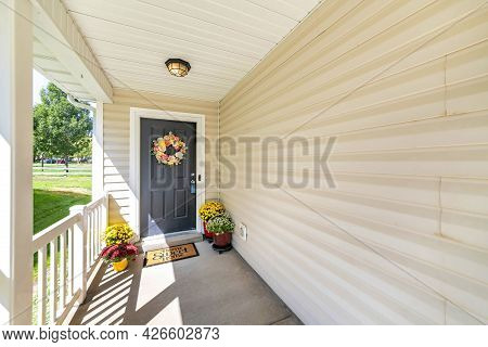 Front Door Porch With Decorative Displays Of Flower Wreath And Potted Flowers At The Floor