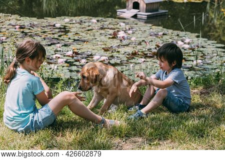 Friendship Of Animals And Children. Girl And Boy, Brother And Sister Are Sitting On The Shore Of The