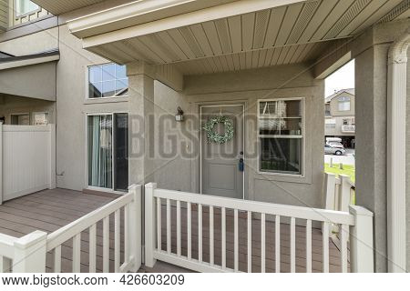 Front Porch Exterior Of A House With Wooden Fence And Door With Wreath