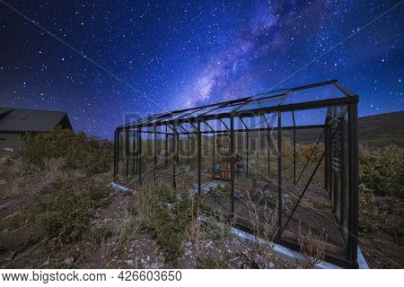 Glass Greenhouse At The Back Of A House Under A Stunning Composite Milky Way Sky