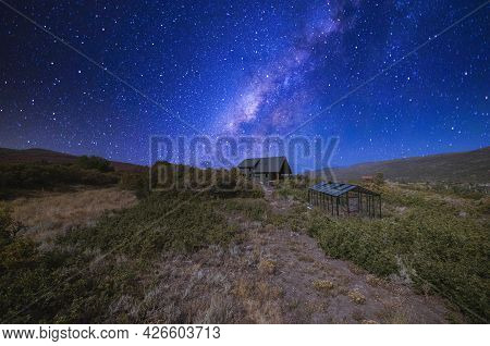 Building Of A House With Glass Greenhouse In The Middle Of A Shrubland Under The Vibrant Night Sky