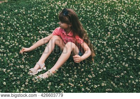 A Cute Adorable Girl Sits On A Clover Meadow And Collects A Bouquet. Rest And Relaxation In Nature.