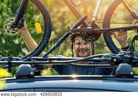 Smiling Cyclist Mounting His Bike On The Car Roof Rack