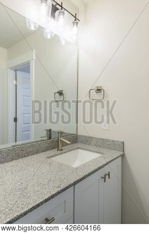 Vanity Sink Of A Bathroom With Granite Countertop And Wall Mounted Lights