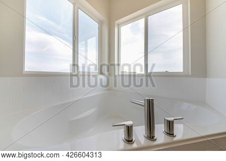 Corner Bathtub In A Bathroom With Widespread Faucet Against The Windows