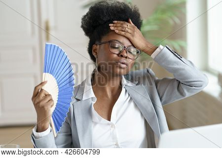 Unwell Millennial African American Woman Hold Waver Feel Sick And Overheated Work On Computer At Hom