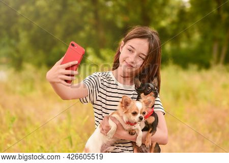 A Young Girl Makes A Selfie On A Smartphone With Dogs In Nature. Teenager And Animals.