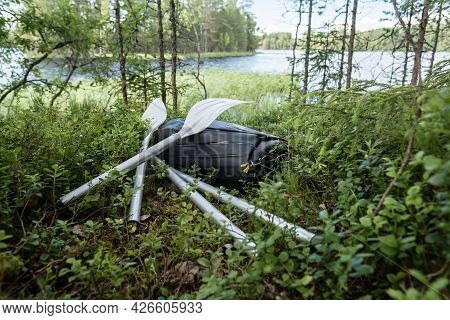 New Rubber Inflatable Boat And Oars Lie In The Grass, On The Shore Of The Lake. Preparing For A Boat