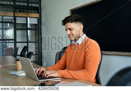 Young Indian Latin Happy Smiling Student Programmer Developer At Desk Working Using Pc Laptop Comput
