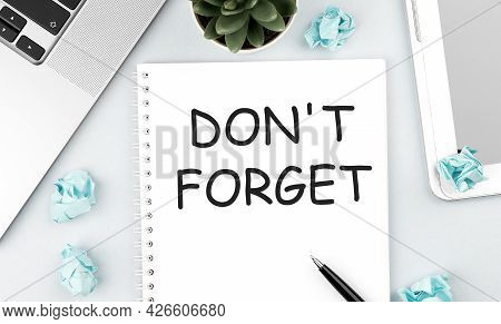 Text Dont Forget On Notebook. Laptop, Pieces Of Paper, Pen And Plant On Office Desk. Flat Lay, Top V