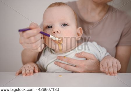 Little Newborn Funny Baby Boy Learning To Eat Vegetable Or Fruit Puree From Glass Jar With Spoon. Yo