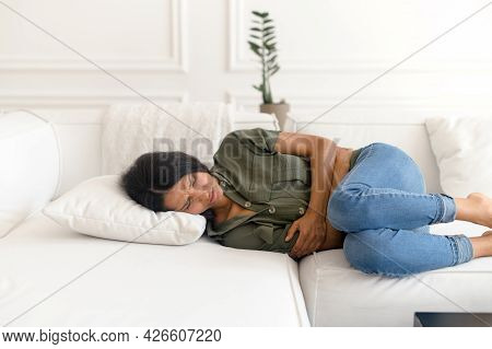 A Young Eastern Woman Lying On The Couch And Suffers From Month Menstruation Period Pain, Stomach Cr