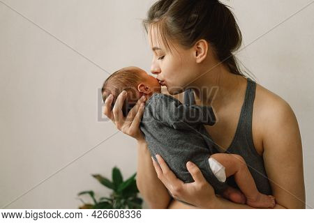 Mother Holds And Hugs Her Newborn Baby Son At Home. Happy Infant And Mom.