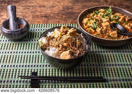 Mapo Tofu In A Bowl Of Rice On A Bamboo Napkin On A Rustic Table With Chopsticks, Bowl With Platter