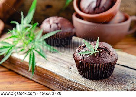 Chocolate Cupcake Muffins With Cannabis Leaves, Weed Cbd. Medical Marijuana Hemp Drugs In Food Desse